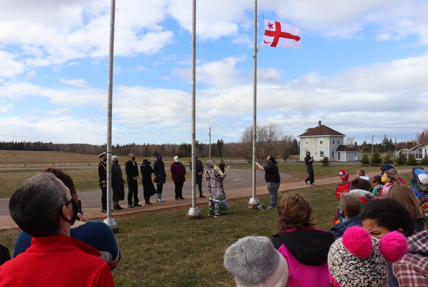Matthew Knockwood raises the Mi'kmaq Grand Council flag as his mother, Methilda Knockwood, sings and drums.