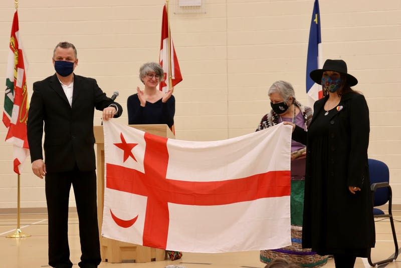 Sylvain Gagné, left, Andréa Deveau, Methilda Knockwood, elder, and Lennox Island Chief Darlene Bernard present the Mi'kmaq Grand Council flag. - Logan MacLean