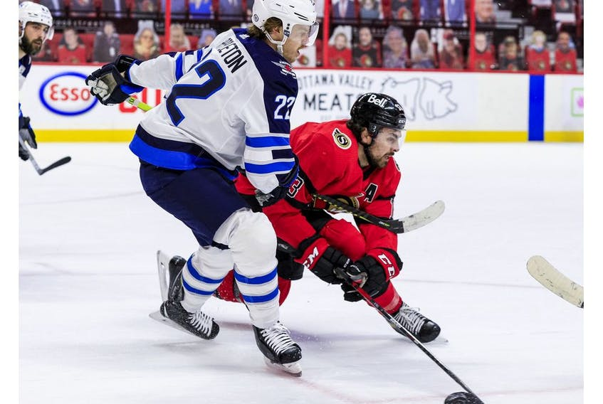 Ottawa Senators left wing Nick Paul (13) battles for a loose puck with Winnipeg Jets centre Mason Appleton, April 14, 2021.