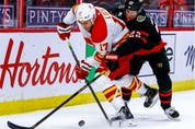 Ottawa Senators defenceman Nikita Zaitsev defends against Calgary Flames left-winger Milan Lucic.