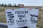 Maria Allen holds up a sign during a protest at the Nova Scotia border on Sunday afternoon. Darrell Cole - SaltWire Network