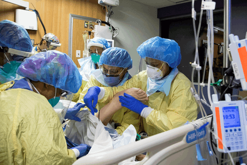 A respiratory therapist and six nurses with a COVID-19 patient inside the intensive care unit of Humber River Hospital in Toronto, April 19, 2021.
