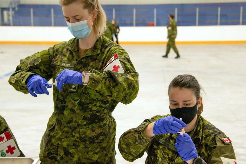 Lt. Samantha O'Keefe, left, and Cpl. Carole-Anne Laroche, both from 1 Canadian Field Hospital, prepare to administer vaccinations to Garrison Petawawa Canadian Armed Forces members.