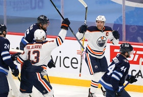 Edmonton Oilers centre Connor McDavid (right) celebrates his goal against the Winnipeg Jets with teammate Jesse Puljujarvi in Winnipeg on Mon., April 26, 2021.