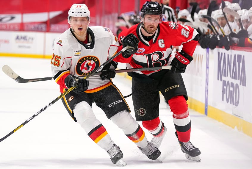Logan Shaw of Glace Bay, right, tries to skate past Stockton Heat forward Eetu Tuulola during American Hockey League action at the Canadian Tire Centre in Kanata, Ont. Shaw currently has five goals and nine points in 15 games. Contributed • Freestyle Photography, Belleville Senators.