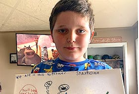 Kyrin Matthews, 7, of Sydney Mines, holds up a picture he drew to promote the importance of following public health directives. Matthews, who was a close contact with someone who was an active COVID-19 case at Shipyard Elementary School, is now self-isolating at home and said everyone has to stay home now as if not they might get COVID-19 and took to art to remind people of the important steps.