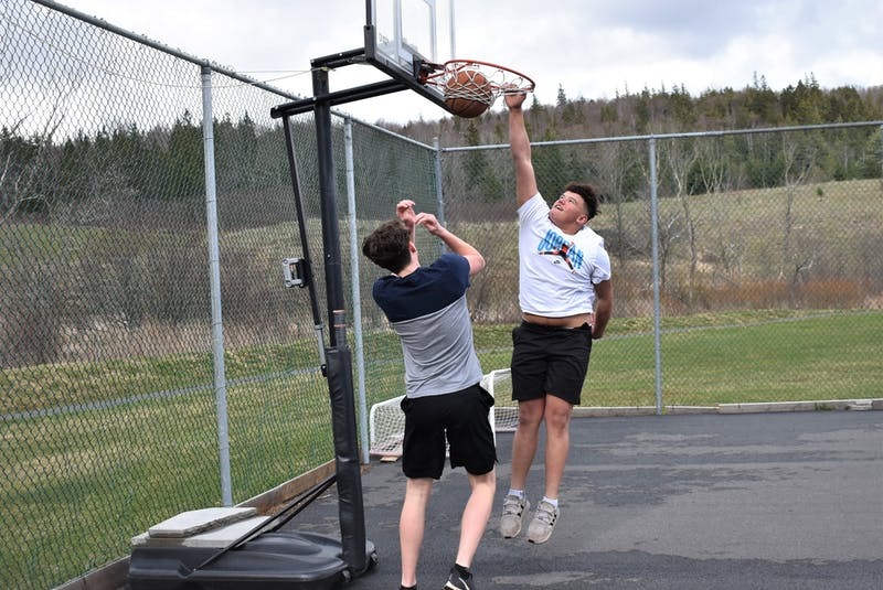 North Nova Education Centre Gryphon Seth Fraser gets a sample of what made his friend and teammate Carmelo Desmond such a tough guy to handle around the basket for their opponents, as the two recently enjoyed a game of one-on-one at the Springville outdoor court.   - Richard MacKenzie