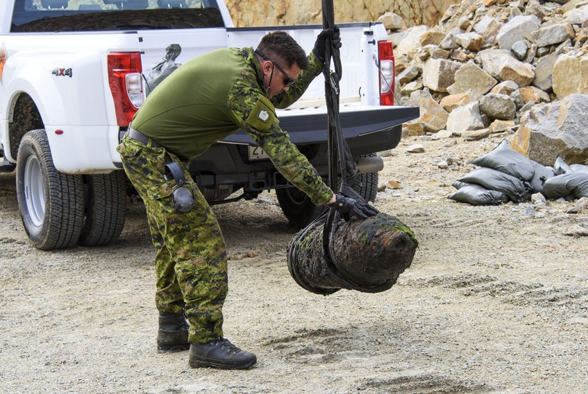 Petty Officer Second Class Tom Amos, guides the UXO to its final position at the disposal site PHOTO: MASTER CORPORAL IAN THOMPSON, CANADIAN ARMED FORCES