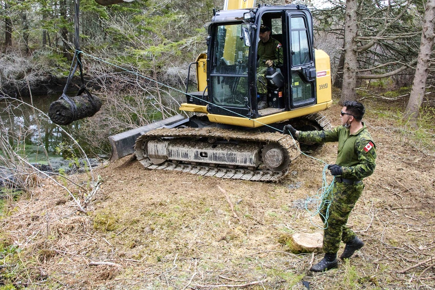 Petty Officer Second Class Tom Amos, guides the UXO as Petty Officer First Class Barry Noseworthy uses an excavator to remove it from the pond and prepared for transport to the disposal site.  PHOTO: MASTER CORPORAL IAN THOMPSON, CANADIAN ARMED FORCES - Saltwire network