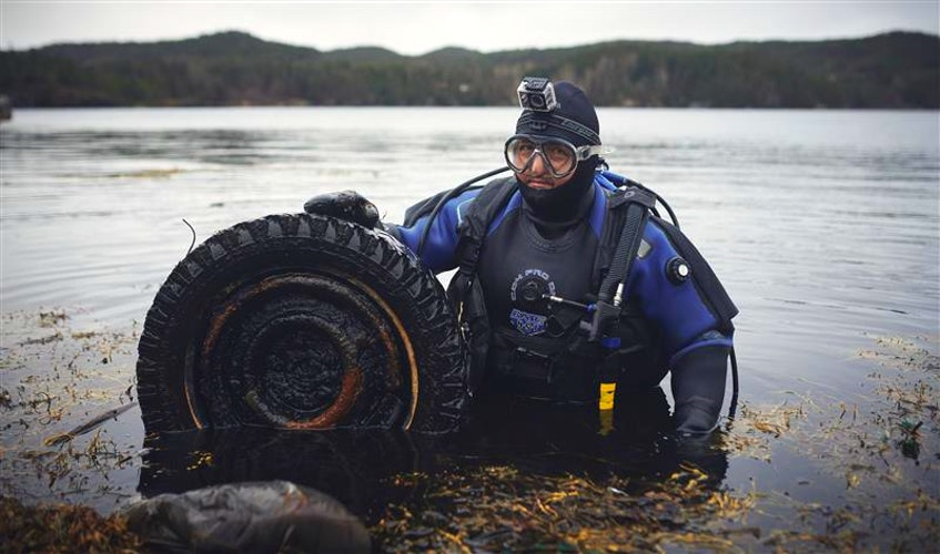 Twillingate resident Shawn Bath pulls an old tire from the ocean in his newest documentary, Hell or Clean Water, which debuted April 29. - Contributed