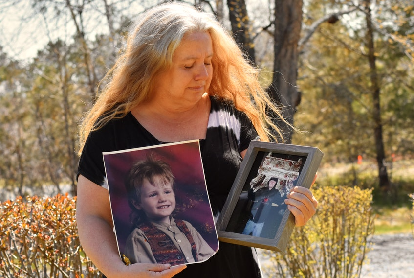 Lori Phillips gets emotional while remembering how excited her late son, Aaron Cogswell, was to find the chair he's carrying in one of the photos she's holding. Cogswell was thrilled to find the chair for his sister, who was moving into a new place. – Ashley Thompson