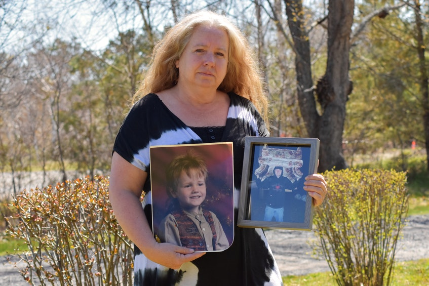 Lori Phillips of Cambridge holds photographs of her late son, Aaron Cogswell. Cogswell was lost at sea after the Chief William Saulis scallop dragger sank off of the coast of Delaps Cove in December 2020. – Ashley Thompson