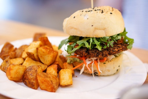 The Veggie Burger with a quinoa and black bean patty and many saucy accoutrements.