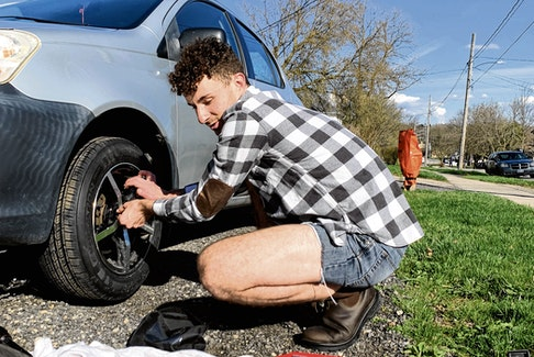 Jacob Maxwell changing from winter tires to summer ones in the driveway of the student house where he rents a room.
