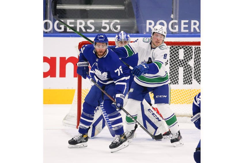 Toronto Maple Leafs T.J. Brodie D (78) defends in front of the net with Vancouver Canucks Brock Boeser LW (6) during the second period in Toronto on Thursday April 29, 2021. Jack Boland/Toronto Sun/Postmedia Network