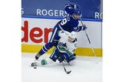 Toronto Maple Leafs Jason Spezza C (19) checks Vancouver Canucks Nils Hoglander LW (36) off the puck during the third period in Toronto on Thursday April 29, 2021. Jack Boland/Toronto Sun/Postmedia Network