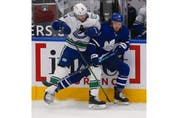 Vancouver Canucks J.T. Miller C (9) takes out Toronto Maple Leafs Justin Holl (3) along the boards during the first period in Toronto on Thursday April 29, 2021. Jack Boland/Toronto Sun/Postmedia Network