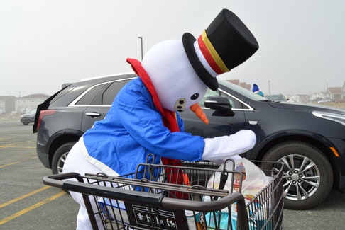 """Even Frosty Festival mascot """"Frosty"""" was on hand to volunteer at Saturday's food drive.  -Joe Gibbons/The Telegram"""