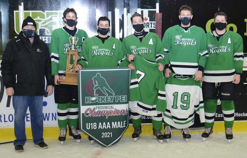The Western Regals accepted the P.E.I. Major Under-18 AAA Hockey League trophy Saturday from Hockey P.E.I. representative Robert MacMillan. The Regals held Ethan Reilly's No. 7 and Alex Hutchinson's No. 19 jerseys during the presentation. From left are MacMillan, Michael McRae, Sam Hackett, Jack Reilly, Carson Wood and Cody McCormick. - Jason Malloy • The Guardian