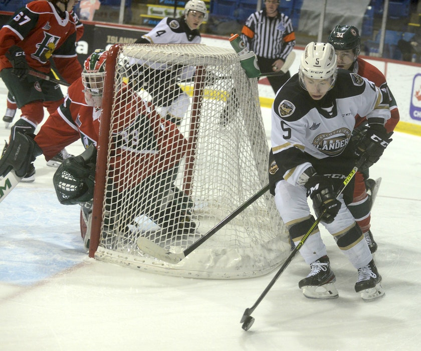 Charlottetown Islanders defenceman Braeden Virtue carries the puck around the Halifax Mooseheads net while being pursued by Mooseheads centre Elliot Desnoyers during the first period of Sunday's Quebec Major Junior Hockey League game at the Eastlink Centre in Charlottetown. - Jason Malloy