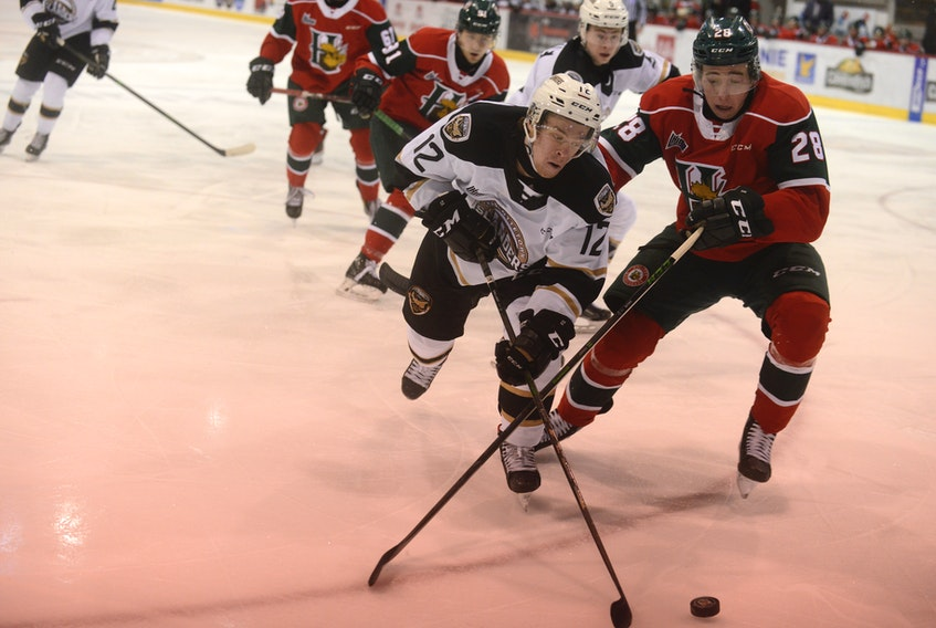Charlottetown Islanders winger Keiran Gallant, left, looks to play the puck behind the Halifax Mooesheads net while Stephen Davis defends Sunday during Quebec Major Junior Hockey League action in Charlottetown.