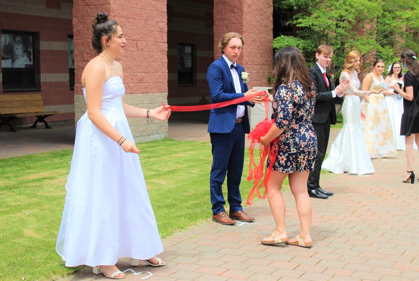 Glace Bay High School's grand march was held at CBU last year since the COVID-19 pandemic forced the cancellation of tradition prom events. From left, then 17-year-old Vittoria Amoria from Terni, Italy, and then 18-year-old Bryson Aucoin, are given the ribbon they must hold to ensure they stay six feet apart from Sandra Johnson, a volunteer parent. CAPE BRETON POST FILE PHOTO