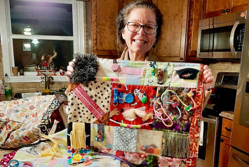 Sonia Myers, social worker with the Senior Mental Health Resource Team, showing off one of the fidget quilts made by Faith LeClair's sewing class.