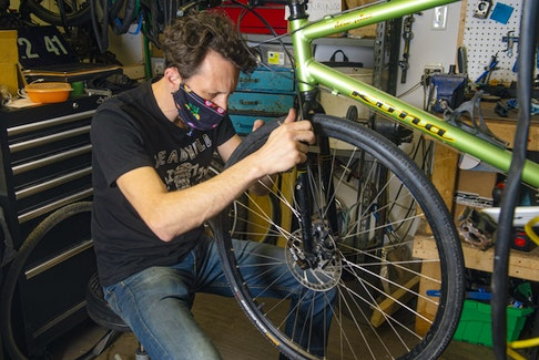 Roger Nelson, co-owner of Halifax Cycles & Guitars, works on a bike in his Halifax shop on Tuesday.