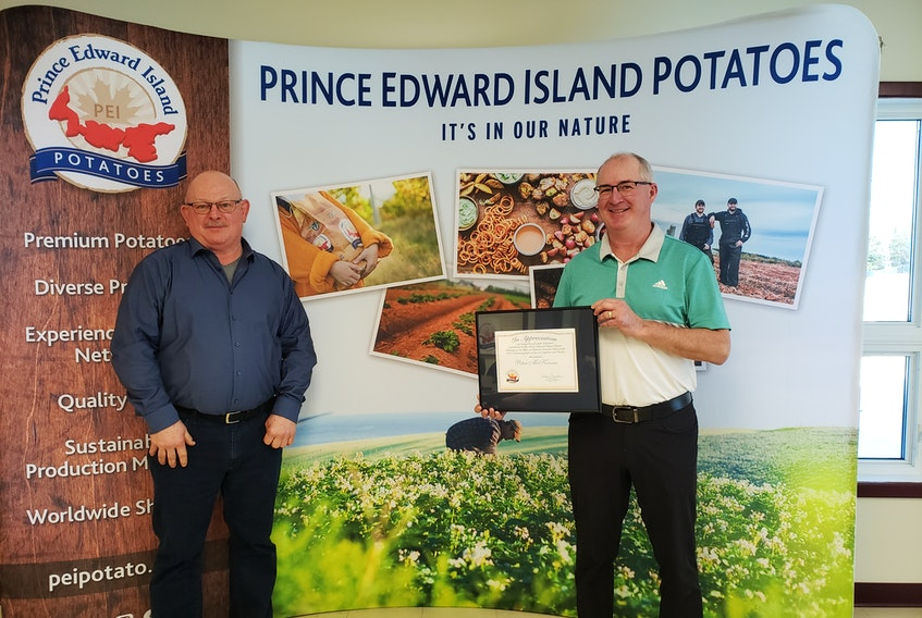 From left to right: PEI Potato Board Chairman Wayne Townshend presents Potato Industry Recognition Award to Peter McKenna .
