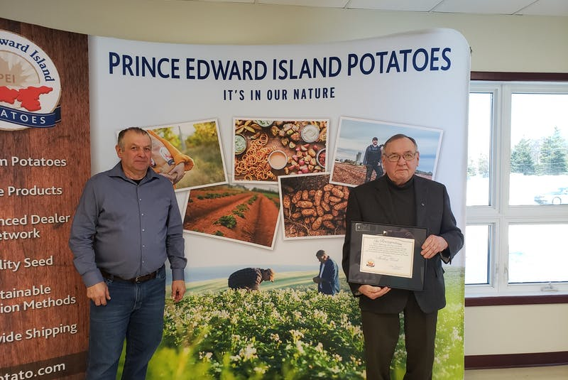 P.E.I. Potato Board director Donald Stavert, left, presents a potato industry recognition award to Morley Wood. - Contributed