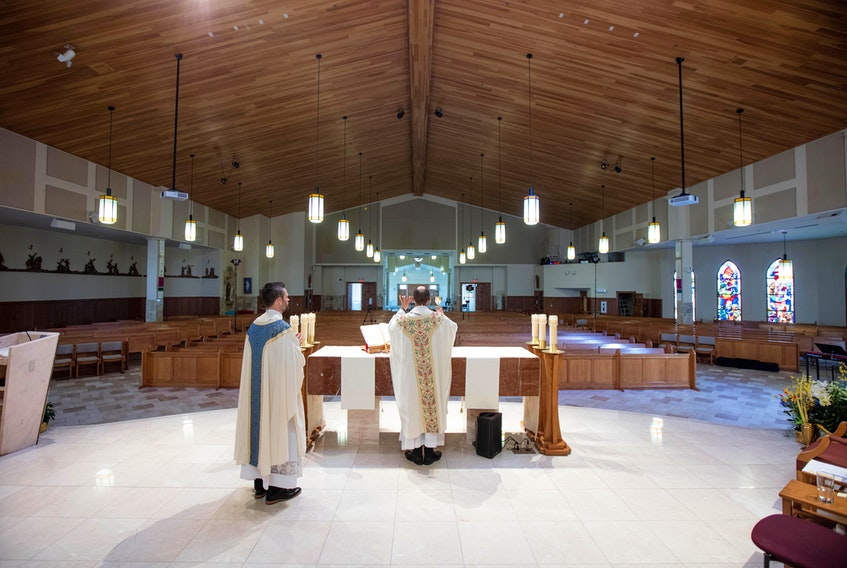 Father Simon Lobo, right, and Father Alex Colautti perform Easter mass at Saint Benedict in 2020. Because places of worship were closed during the first wave of COVID, the parish live-streamed the mass to more than 16,000 viewers. A year later, places of worship are still capped at 50 per cent of the building's capacity up to 100 people, while big stores are allowed to accommodate larger crowds. – Len Wagg