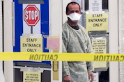 A health care worker stands outside a SARS assessment entrance at York Central Hospital in Richmond Hill, Ont., April 21, 2003.
