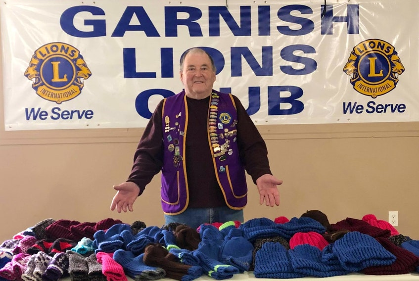Garnish Lions Club president Morgan Pardy displays the items collected so far this year as part of its knitting project. The pieces will eventually be distributed to homeless and other vulnerable people in the province.  CONTRIBUTED