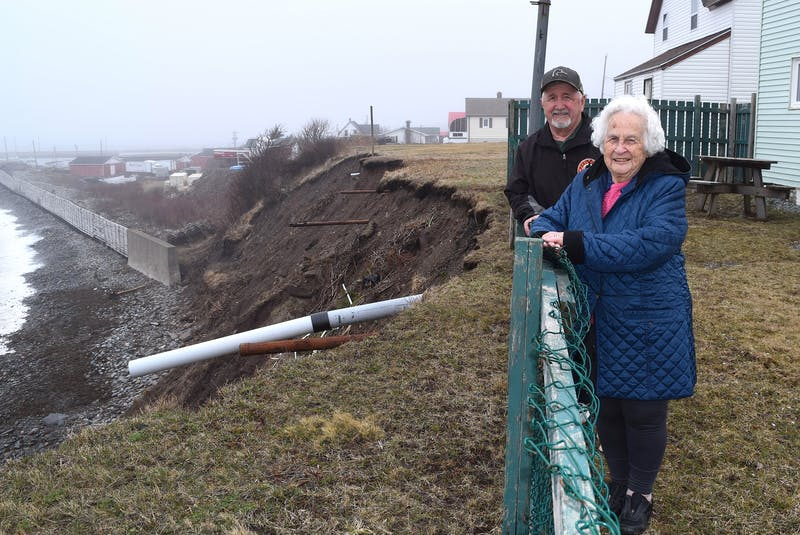 Stan Peach of Glace Bay stands with his mother Joyce Peach in her backyard in Port Morien that overlooks a 50-foot cliff. Stan estimates over the years 75 feet of land has been lost to erosion and says he worries about his mother who is living only 15 feet from the cliff edge. Sharon Montgomery-Dupe/Cape Breton Post