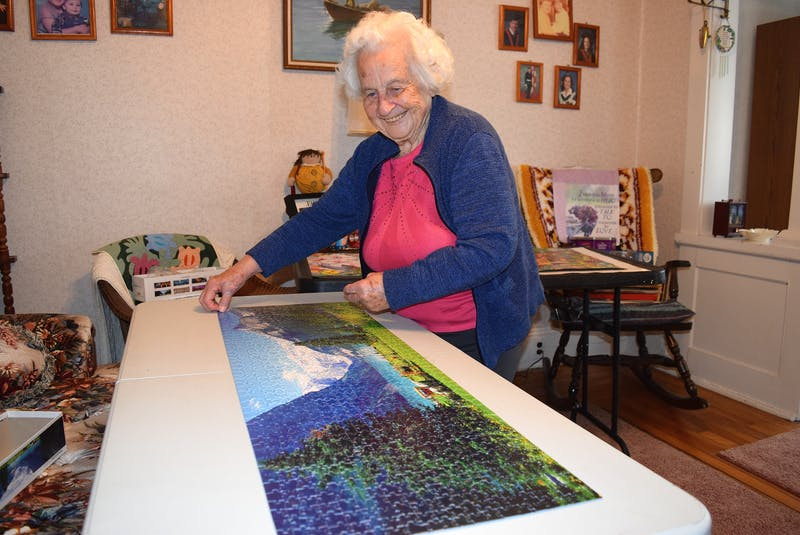 Joyce Peach of Peach Street, Port Morien, with her favourite pastime — making jigsaw puzzles. Joyce says living near the edge of the cliff doesn't bother her, it's her home and she'll never leave. Sharon Montgomery-Dupe/Cape Breton Post
