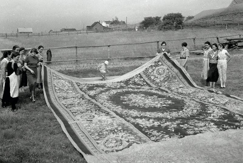 "American artist Lillian Burke, left with short bob hairstyle , with a ""Savonnerie"" designed rug based on an original 17th-century carpet in the Louvre. It was reputed to be the largest hooked rug ever created (648 sq.ft.) and was made by nine women over a six-month period under the direction of Mme Annie á Joseph Chiasson. -  Dr. David Fairchild, Wikipedia Creative Commons."