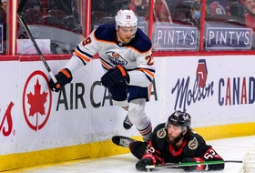Ottawa Senators center Clark Bishop (62) checks Edmonton Oilers center Leon Draisaitl (29) during second period NHL action at the Canadian Tire Centre in Ottawa on April 7, 2021.