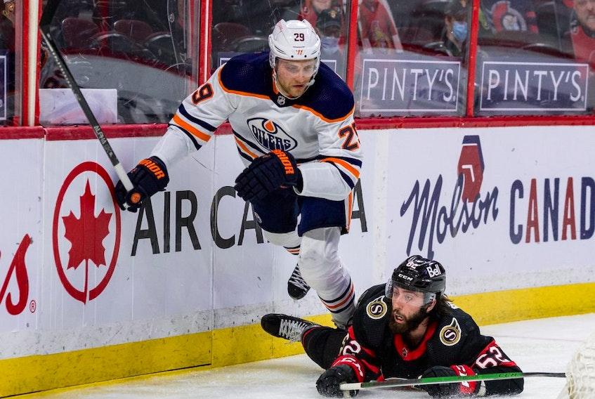 Ottawa Senators center Clark Bishop (62) checks Edmonton Oilers center Leon Draisaitl (29) during second period NHL action at the Canadian Tire Centre in Ottawa on April 7, 2021.