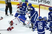 Montreal Canadiens' Phillip Danault is flattened by Maple Leafs' Morgan Rielly after slamming into goalie Jack Campbell during a scramble in front of the net during the third period in Toronto on Wednesday, April 7, 2021.