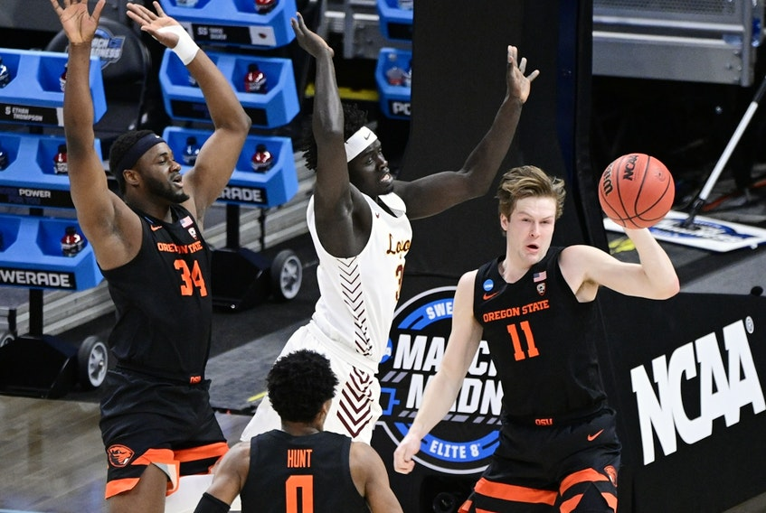 Oregon State Beavers guard Zach Reichle (11) passes the ball against Loyola University of Chicago Ramblers forward Aher Uguak (middle), who is swarmed by Oregon State forward Rodrigue Andela (34) and guard Gianni Hunt (0) during the Sweet 16 of the 2021 NCAA tournament at Bankers Life Fieldhouse in Indianapolis on March 27, 2021.