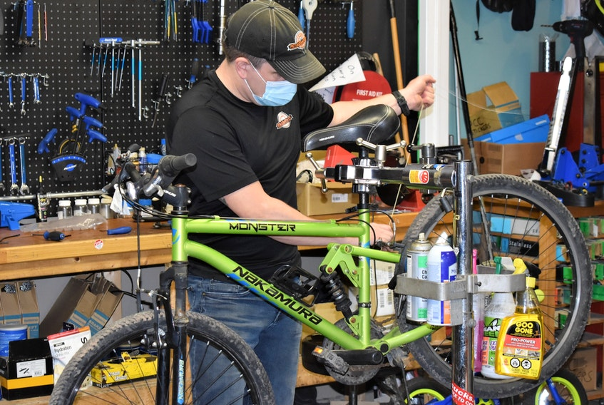Pictou County Cycle owner Clint Snell working on a bike. The service part of his business has been busy and the retail part as well, but it has been impacted greatly by a lack of product.