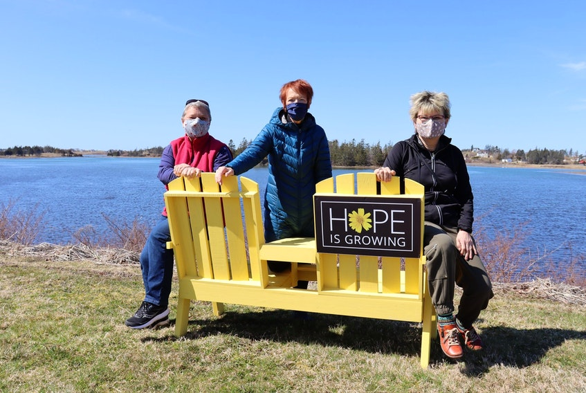 Communities in Bloom members Alvina Robicheau, Jean Clulee and President Heather Hatfield with one of eight yellow benches set up around Yarmouth in the name of hope