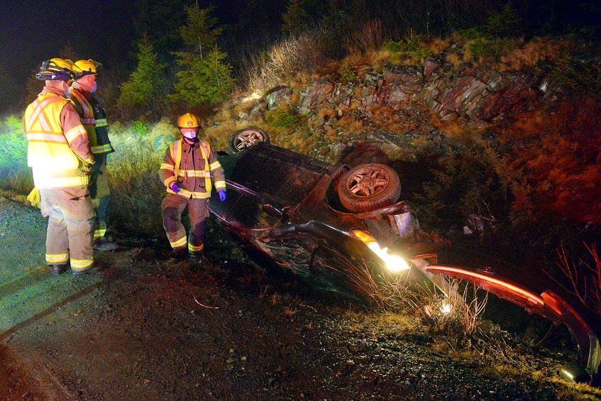 A woman escaped serious injuries after the car she was driving overturned on Peacekeepers Way Friday night. Keith Gosse/The Telegram