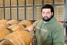 Assistant winemaker Alex Morozov in the barrel room at Benjamin Bridge with a bottle of the wine that spent a year submerged.