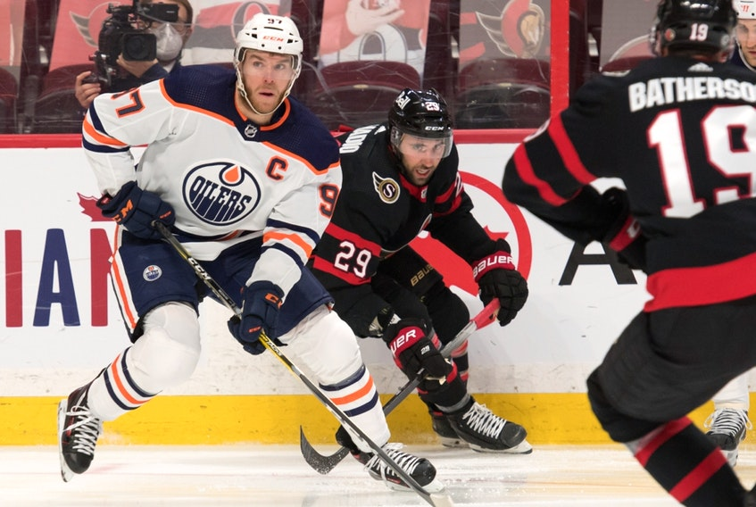 Edmonton Oilers centre Connor McDavid (97) carries the puck ahead of Ottawa Senators centre Michael Amadio (29) at the Canadian Tire Centre on Thursday, April 8, 2021.