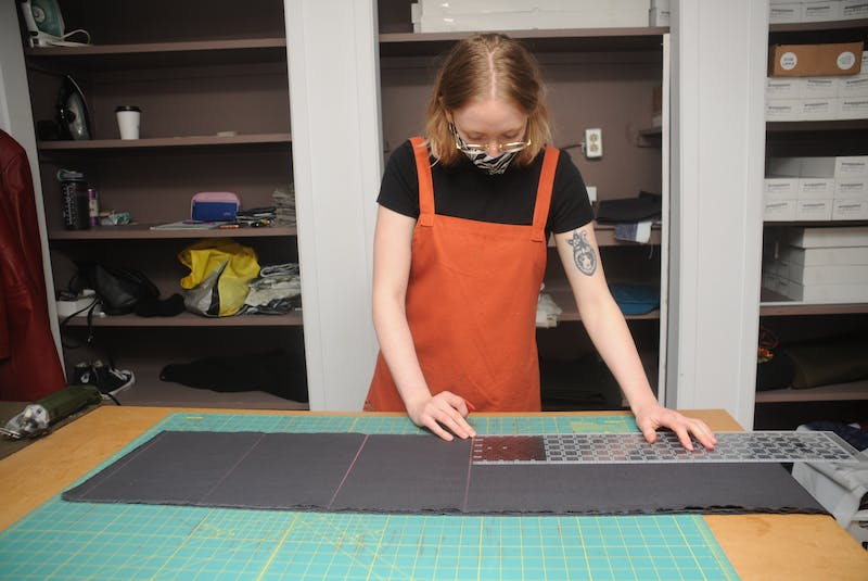 Kali Kenny cuts fabric to make lining for Ragmaw bags. — Andrew Robinson/The Telegram