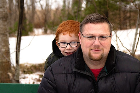Alex McConnachie, pictured with son Kaiden, thinks everyone should have a phone and he is doing something about it. CONTRIBUTED