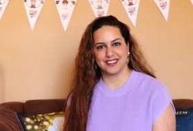 Farah Al-behadili sits in front of a Ramadan banner, with holiday cushions beside her.