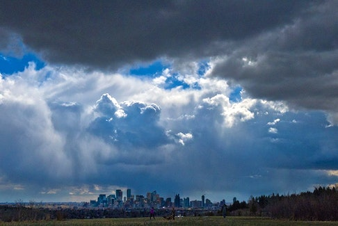 Storm clouds move in over walkers in Edworthy Park and the downtown Calgary skyline on Tuesday, May 4, 2021.
