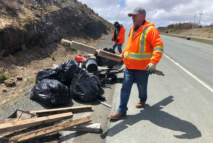 Among the Transportation and Infrastructure employees cleaning up the Outer Ring Road on Sunday were Harold Cobb and Derek George, pictured near the Team Gushue  Highway exit piling garbage for pickup. Joe Gibbons • The Telegram